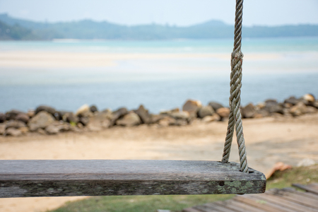 Old wooden swing on the beach