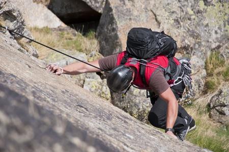 climber while climbing a vertical rock wall