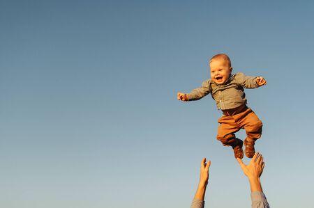 Foto de Happy baby boy because his father is throwing him up to the sky. Background of the sky - Imagen libre de derechos