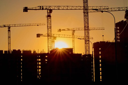 Photo for construction of the building cranes in the strongest light, otherwise from the sun - Royalty Free Image