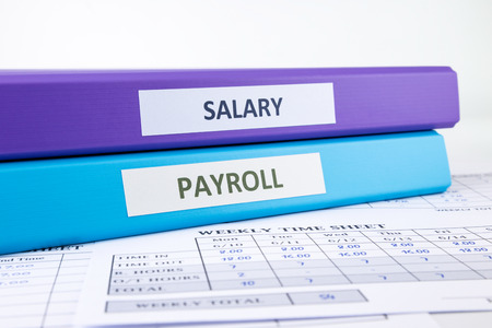 PAYROLL and SALARY word on binder place on weekly time sheet documents, human resources concept