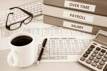 Human resources documents: payroll, salary and employee  time sheets place on office table with cup of coffee and calculator, sepia tone