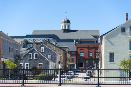 Photo pour New Bedford, Massachusetts, USA - September 25, 2016: New Bedford Whaling Museum looms over old buildings along the Acushnet River waterfront - image libre de droit