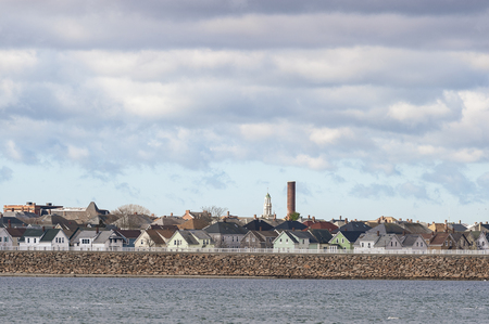 Photo pour Smokestack and church steeple stand out over New Bedford neighborhood behind hurricane protection barrier - image libre de droit