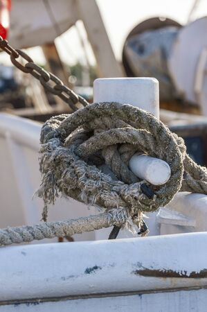 Photo pour Bollard wrapped with worn line securing commercial fishing boat to dock - image libre de droit
