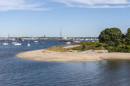 Photo pour Moored boats lying off curving beach on Palmer Island in New Bedford inner harbor - image libre de droit