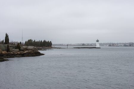 Photo pour Palmer Island lighthouse and Fairhaven waterfront on foggy morning in New Bedford harbor - image libre de droit