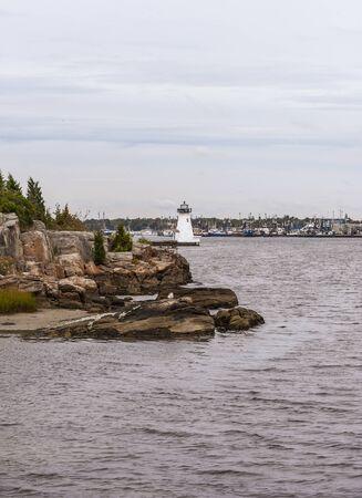 Photo pour Palmer Island rocky shoreline and lighthouse in New Bedford harbor - image libre de droit