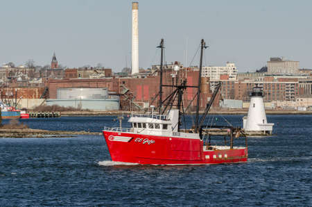 New Bedford, Massachusetts, USA - March 14, 2020: Scallop dragger El Jefe, hailing port New Bern, NC, passing lighthouse on her way out of New Bedford