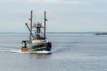 New Bedford, Massachusetts, USA - August 15, 2018: Commercial fishing vessel Capt. Bob, hailing port Cape May, NJ, coming out of foggy Buzzards Bay