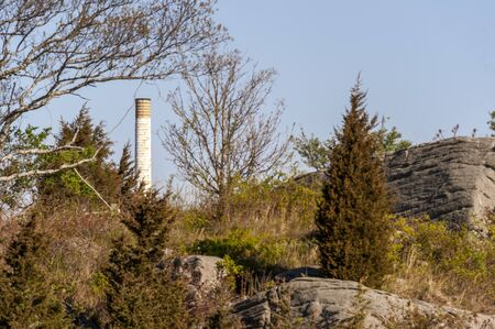 Photo pour Smokestack at decommissioned New Bedford Gas and Edison Light Complex standing tall over Palmer Island hillside - image libre de droit