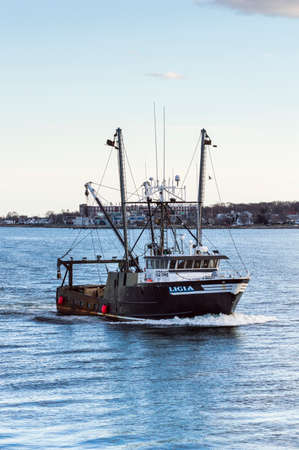 Photo pour New Bedford, Massachusetts, USA - March 11, 2018: Commercial fishing vessel Ligia approaching New Bedford inner harbor on evening in late winter - image libre de droit