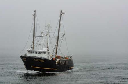 Photo pour New Bedford, Massachusetts, USA - April 4, 2018: Fishing vessel Westport approaching hurricane barrier through fog in New Bedford inner harbor - image libre de droit