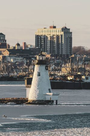 Photo pour Icy water surrounding Palmer Island Light Station with New Bedford waterfront in background - image libre de droit