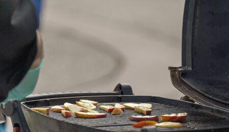 Photo pour Chef cooking slices of apple on a grille - image libre de droit