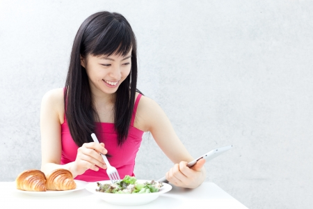 beautiful young girl eating breakfast and using tablet computer