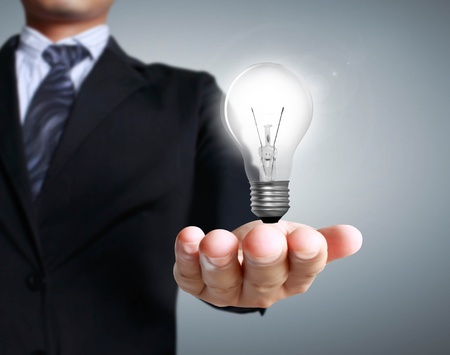 Light bulb in a hand on a gray background