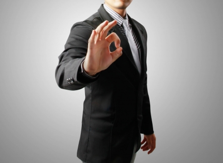 business man with hand OK gesture on the gray background