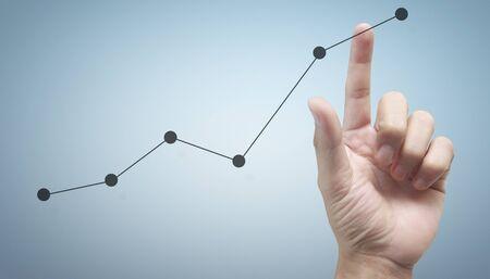 Foto de Hand touching a graphs of financial indicator and accounting market economy analysis chart - Imagen libre de derechos