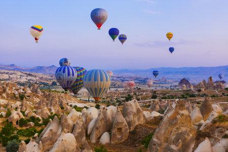 Photo pour Cappadocia, Turkey - August 31, 2011: Hot air balloon flying over rocky landscape at sunrise in Cappadocia. - image libre de droit