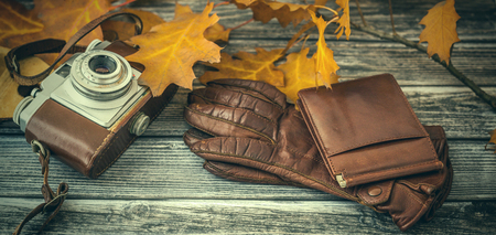 Closeup of leather gloves, wallet and photo camera on vintage wooden background
