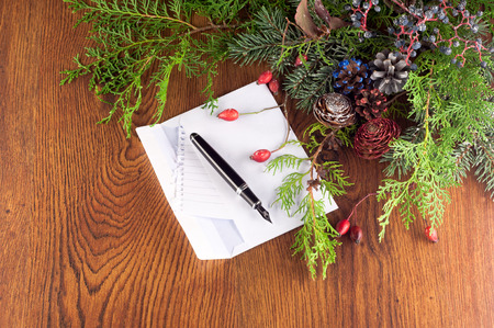 Christmas decoration with a letter to Santa and pine branches on a wooden board