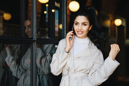 Lovely brunette woman with wavy hair tied in pony tail having good-looking pale face looking elegantly while posing outdoors using modern gadget. Cute young female dressed in fashionable clothes