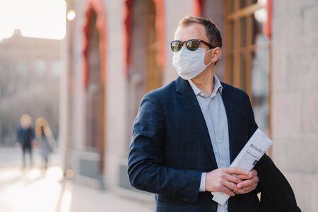 Photo pour Working in pandemic situation. Business worker or entrepreneur wears medical mask for coronavirus protection stands beside office building outdoor holds newspapers concentrated somewhere into distance - image libre de droit