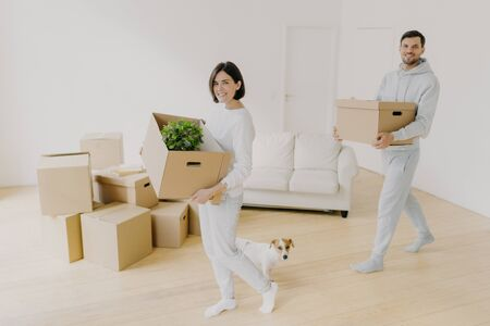 Photo of happy smiling brunette woman and her husband carry cardboard boxes with personal belongings, relocare to new apartment, enter empty room, start new life, little dog near, enjoy moving day