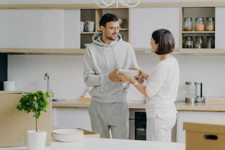 Photo pour Photo of happy husband and wife unpack things after moving into new house, carry white plates, pose against kitchen interior, have fun, dressed in domestic clothes. People and moving concept - image libre de droit