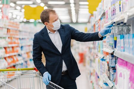 Photo pour Image of man consumer buys detergent in shopping mall, takes bottle of washing gel in cart, chooses household products, cares about hygiene and protection during pandemic situation, virus spread - image libre de droit