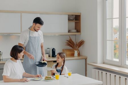 Photo pour Father prepared fried eggs for family, little child holds plate and waits for breakfast. Family pose at kitchen near table, enjoy tasty meal, have glad expressions. People, eating, domestic atmosphere - image libre de droit