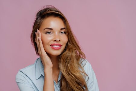 Photo pour Photo of pleasant looking female model touches cheeks with palm, has gentle toothy smile, wears makeup, dressed in casual shirt, stands against purple wall, copy space area for your advertisement - image libre de droit