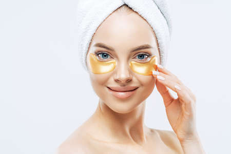 Photo pour Close up shot of happy tender woman applies golden patches under eyes, removes wrinkles and dark circles, has manicure, wears towel on head, isolated over white background. Beauty treatment concept - image libre de droit