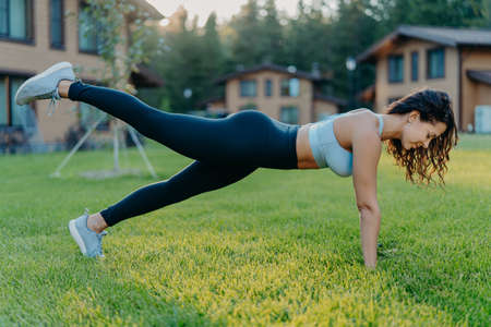Slim motivated brunette woman does fitness exercises in open air raises legs and has regular workout dressed in cropped top leggings, sneakers, poses on green grass near house. Active rest concept