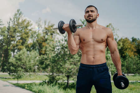 Photo for Horizontal shot of topless fitness unshaven European man has muscular body, raises barbells, wears shorts, demonstrates strong arms, has workout outdoor in park. Sportsman makes weightlifting - Royalty Free Image