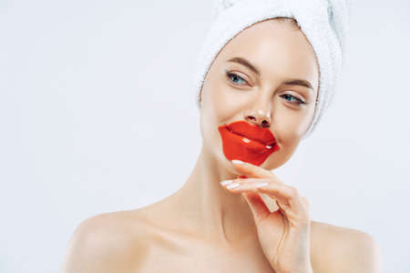 Photo pour Thoughtful beautiful woman wears lip patch, touches jawline gently, has concentrated look aside, enjoys skin care pampering procedure, stands bare shoulders, white background. Cosmetology concept - image libre de droit