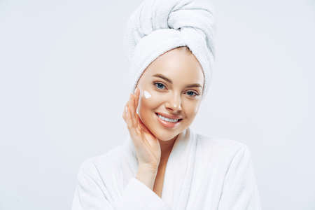 Photo pour Charming relaxed beauty woman applies face cream, cares about complexion, touches cheek with hand, smiles gently at camera, dressed in bath robe, wrapped towel on washed hair, isolated on white - image libre de droit