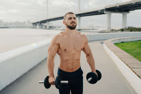 Muscular bodybuilder concentrated into distance has strong body strong muscles holds barbells and does exercises for biceps outdoor poses near river with bridge. Healthy lifestyle and sport concept