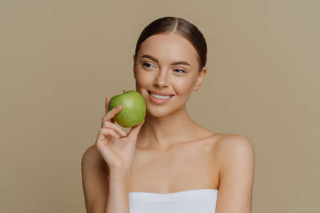 Photo for Thoughtful charming European woman holds apple near face smiles gently has white perfect teeth healthy clean skin wrapped in shower towel stands with bare shoulders against brown background. - Royalty Free Image