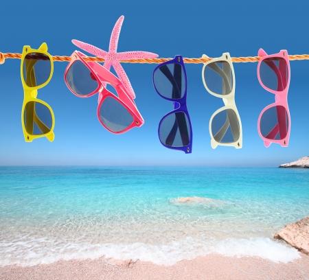 Photo pour Collection of sunglasses on the beach - image libre de droit