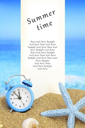 Photo pour Summer time. White banner and alarm clock on the beach - image libre de droit