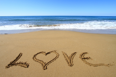 Love written on golden sandy beach