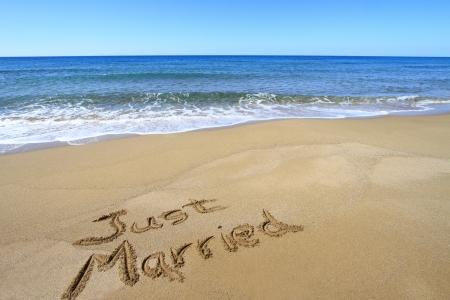 Just married written on golden sandy beach