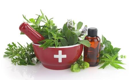 Photo pour Mortar with medicine cross, fresh herbs and essential oil bottle - image libre de droit