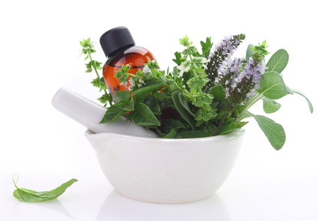 Photo pour Mortar and pestle with fresh herbs and essential oil bottle - image libre de droit