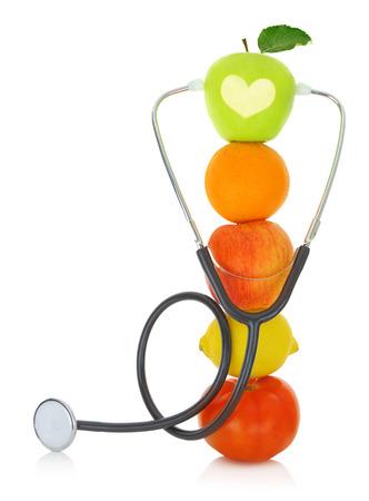 Stethoscope with fresh fruits isolated on white