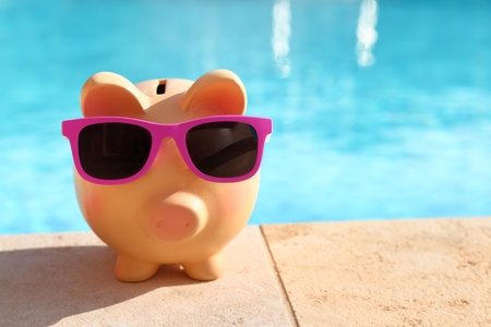 Photo pour Summer piggy bank with sunglasses in front of a swimming pool - image libre de droit