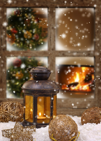 Photo for Christmas lantern and ornaments on snow in front of a window - Royalty Free Image
