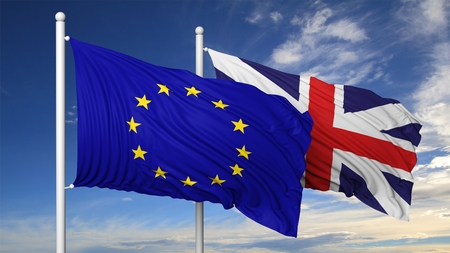 Waving flags of EU and UK on flagpole, on blue sky background.